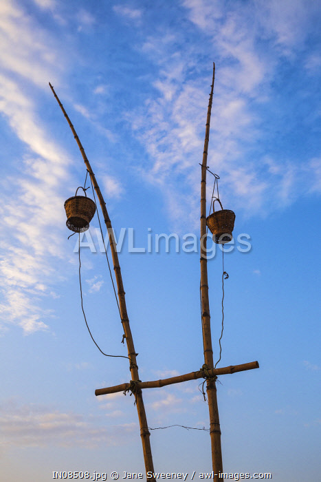 India, Uttar Pradesh, Varanasi, Sindhia Ghat, Wicker baskets on bamboo poles containing lanterns. It is believed that the lights from diya oil lamps will lighten the path for the souls of dead ancestors to reach heaven.