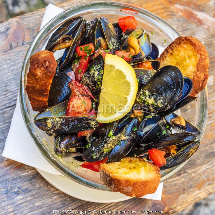 Europe, Italy, Liguria. Genoa, Boccadasse. A plate of mussels Marinara style.
