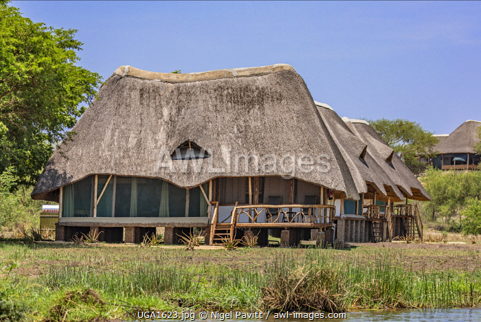 awl-images.com - Uganda / Uganda, Murchison Falls National Park. Accommodation chalets of a luxury lodge on the banks of the Victoria Nile.