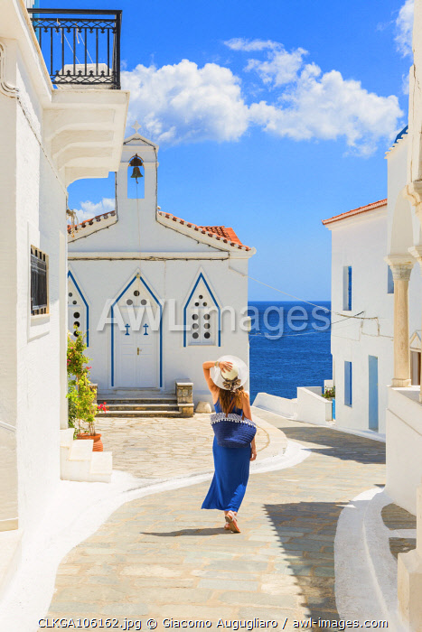 Young woman walking on the street that leads to the Church of St. Barbara, Andros, Cyclades archipelago, Greece, Europe (MR)