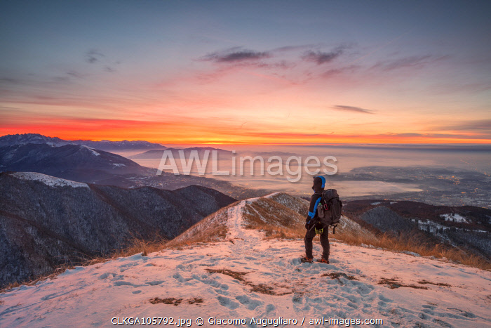 awl-images.com - Italy / Young hiker admiring Brianza view from Bollettone Mount at sunrise, Como province, Lombardy, Italy (MR)