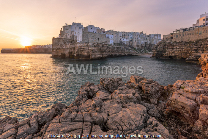 awl-images.com - Italy / Old town of Polignano a Mare built on rocky cliffs at sunrise, Bari province, Apulia region, Italy
