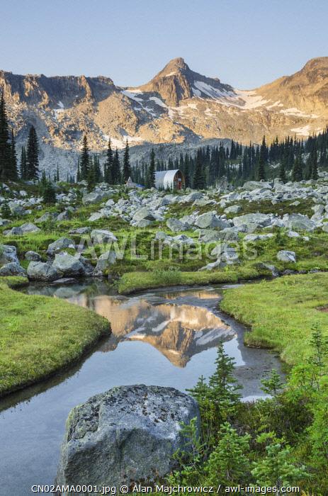 Mountains reflected in creek, subalpine meadows of Marriott Basin, Coast Mountains, British Columbia