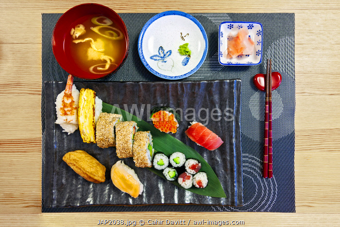 Traditional Japanese Sushi cuisine comprising miso soup, wasabi, ginger, shrimp sushi, tamagoyaki egg roll, Califonia roll, hosomaki, banana leaf and inari age served in traditional style, prepared in a cultural experience class in Shinanomachi, Wakaba, Tokyo To, Japan.