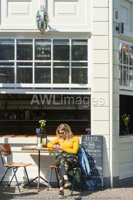 awl-images.com - Netherlands / Netherlands, Northern Holland province, Amsterdam, woman seated at the terrace of a cafe in the Jordaan district