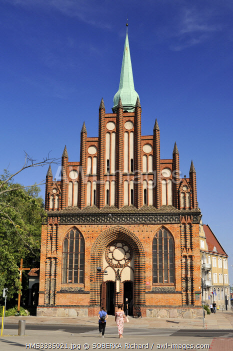 awl-images.com - Poland / Poland, West Pomeranian, Szczecin, monument to the dead of the anti communist revolt of December 1970 in front of the Church of Saint Paul and Saint Peter dating back to 1124 and which is the oldest in Szczecin, tourists in front of the church