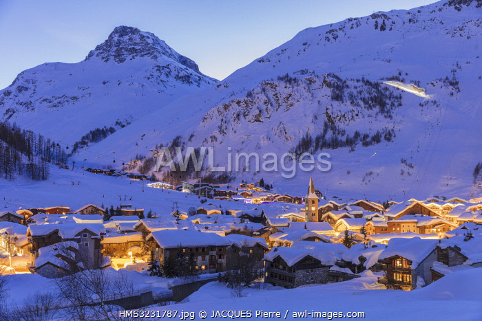 France, Savoie, Val D'Isère, view of the village on a full moon and Saint Bernard de Menthon Church with a squared Lombard bell tower at dusk and the Olympic flank of Bellevarde (2827 m), massif de la Vanoise, hight Tarentaise valley