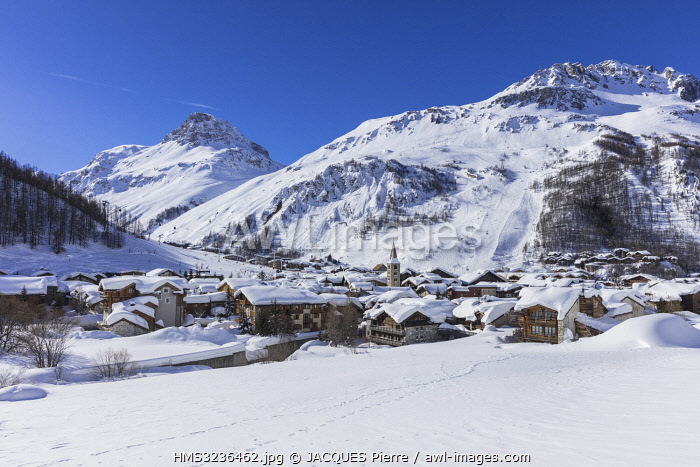 France, Savoie, Val D'Isère, view of the village and Saint Bernard de Menthon Church with a squared Lombard bell tower at dusk and the Olympic flank of Bellevarde (2827 m), massif de la Vanoise, hight Tarentaise valley
