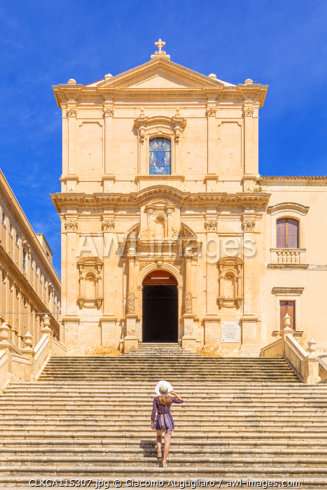 Young woman climbing the stairs of San Francesco all'Immacolata church, Noto, Siracusa province, Sicily, Italy (MR)