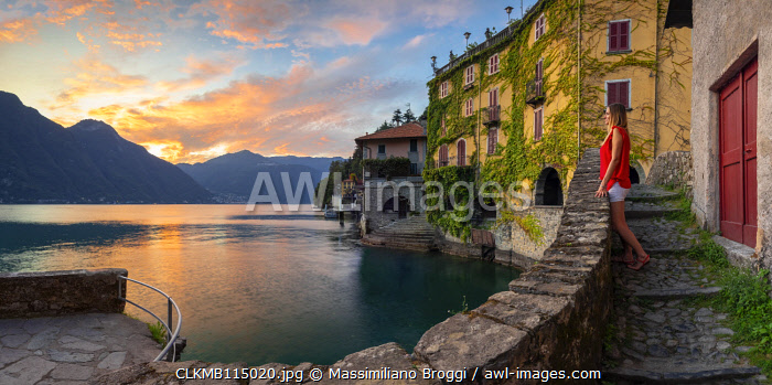 A lady observes sunset at Nesso, Como lake, Como, Lombardy, Italy (MR)