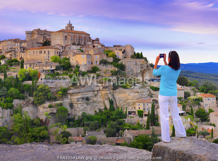 France, Vaucluse, Provence, Gordes, woman standing with camera at viewpoint (MR)