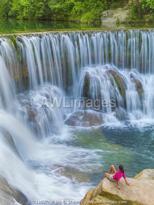 France, Lozere, Longuedoc-Roussillon, Gorges du Tarn, Woman sitting at Waterfall (MR)