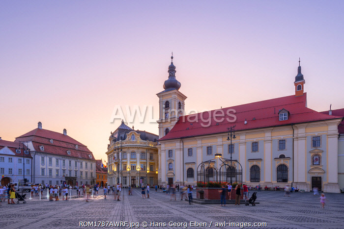 Piata Mare and the Holy Trinity Roman Catholic Church at dusk, Sibiu, Transylvania, Romania