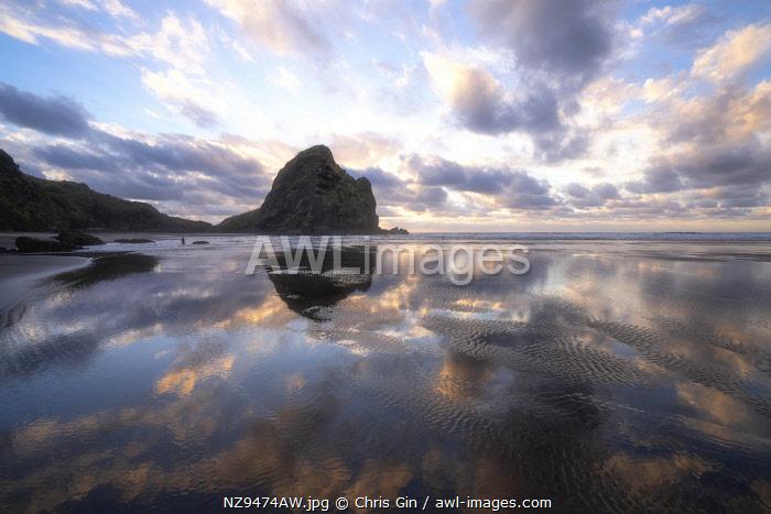 Sunset reflections at Piha Beach, Auckland, New Zealand