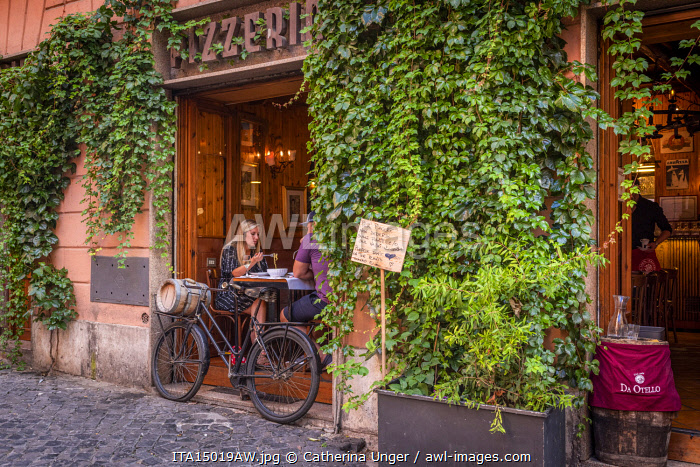 Europe, Italy, Rome. A restaurant in Trastevere with a couple eating spaghetti.