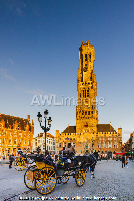 awl-images.com - Belgium / A horse carriage with tourists in front of Bruges Civic Tower, (Bellfroi) at sunset, Belgium