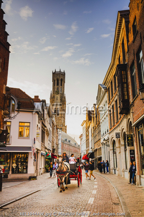 awl-images.com - Belgium / A horse carriage riding in the narrow streets of Bruges old town at sunset, Belgium