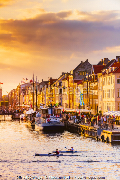 Two people kayaking in the Nyhavn canal in Copenhagen at sunset, Denmark