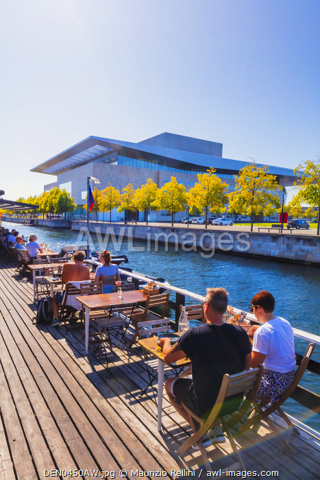 awl-images.com - Denmark / People sitting in a cafe along a water canal with the Opera House in the background in Copenhagen, Denmark