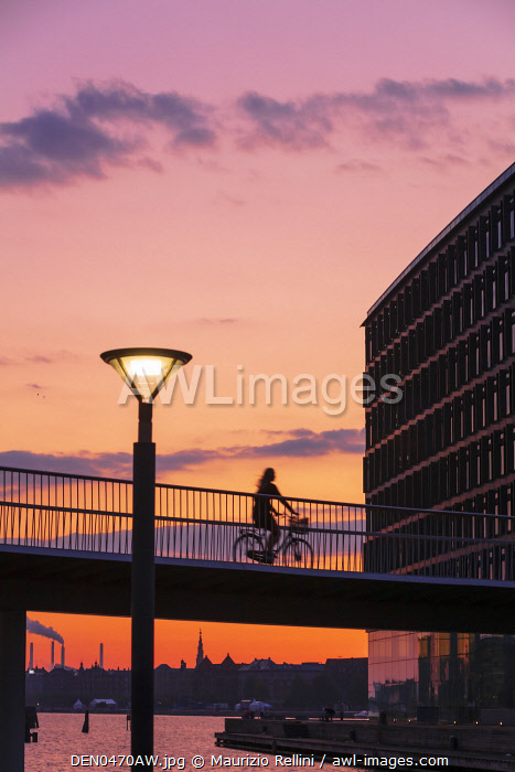 awl-images.com - Denmark / A woman riding a bike on a suspended bridge in Copenhagen at sunset, Denmark