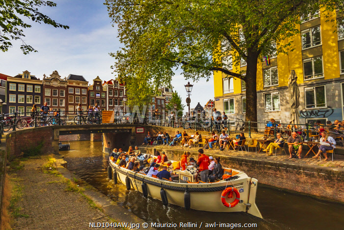 awl-images.com - Netherlands / A boat with tourists in a canal at sunset in Amsterdam, Holland/Netherlands