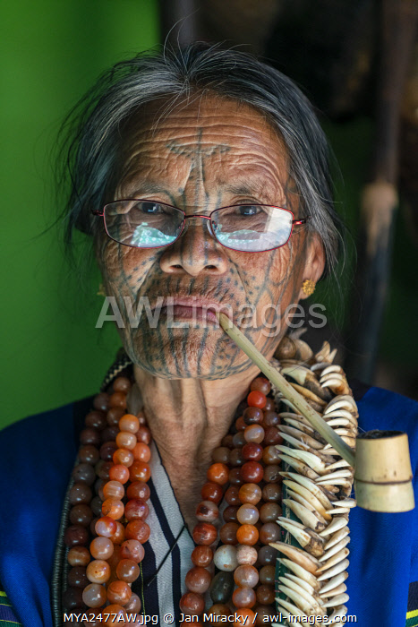 awl-images.com - Myanmar / Close-up portrait of old lady with glasses and traditional facial tattoo smoking a pipe, Mindat, Mindat Township, Mindat District, Chin State, Myanmar