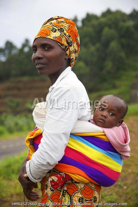 Rwanda, Gisakura, woman wearing a colorful turban and carrying her baby in the back