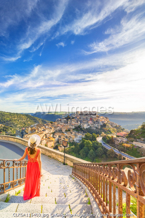 Young woman admiring the enchanting hilltop city of Ragusa Ibla from the stairs of Santa maria delle Scale church, Ragusa, Sicily, Italy  (MR)