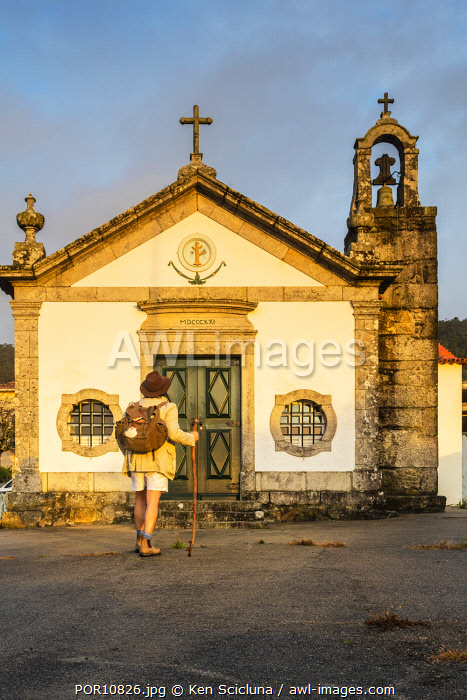 awl-images.com - Portugal / Portugal. Viana do Castelo. Carreco. Pilgrim of Santiago with rucksack shell and stick on the Camino Portuges do Costa walking in the beautiful environs of the Igreja Sao Sebastiao or Church of St Sebastian in the hamlet of Carreco. RM.