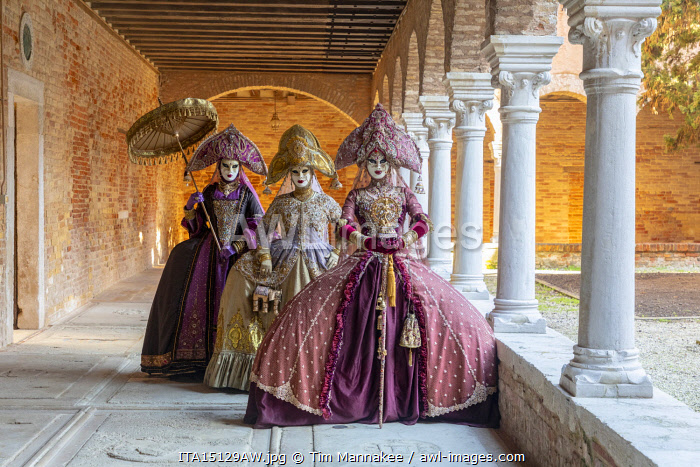 Three women wearing Indian style costumes and masks pose in the cloisters of Chiesa di San Francesco della Vigna, Venice, Veneto, Italy