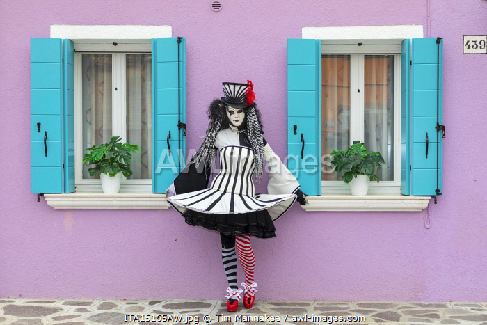 A woman poses in front of a colourful facade on Burano, Venice, Venato, Italy