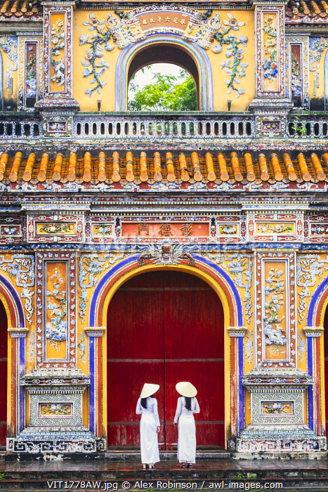Southeast Asia, Vietnam, Hue. Two young women wearing Ao Dai dresses stand next to an elaborately carved gateway to the Purple Citadel in the historical imperial old city and UNESCO world heritage site MR