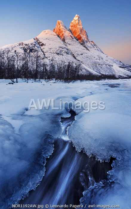 Frozen river and Mt. Otertinden taking the first lights of the day, Tromso region, Norway