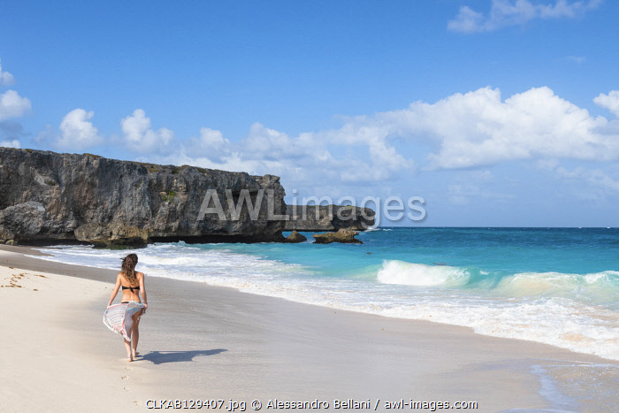 Woman with pareo walks on the beach of Bottom Bay, Barbados Island, Lesser Antilles, West Indies