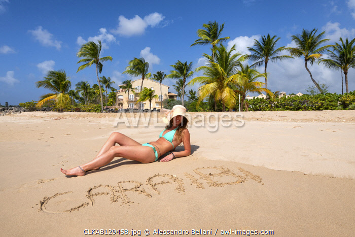 Girl Sunbathes on the beach behind the written Caraibi  Heywoods Beach, Barbados Island, Lesser Antilles, West Indies