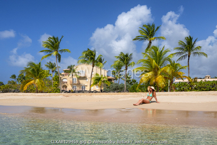 Girl sunbathes on the beach facing the turquoise water of the Caribbean sea, Heywoods Beach, Barbados Island, Lesser Antilles, West Indies