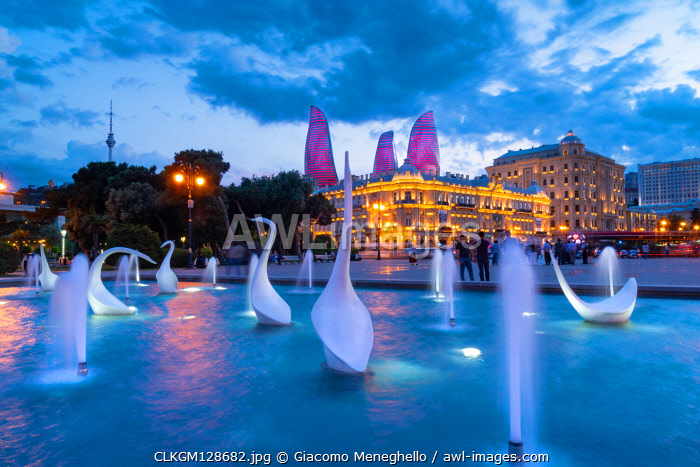 A swans fountain in the Baki Bulvari with Flame Towers in the background at twilight. Baku, Azerbaijan, Central Asia.