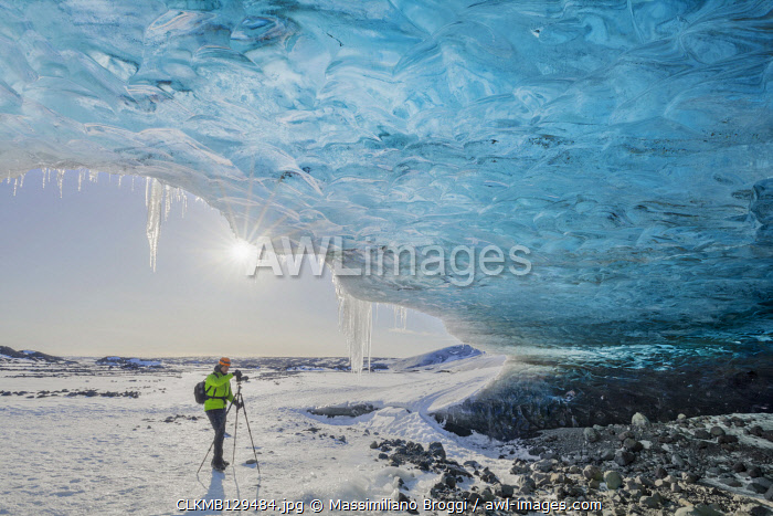Man photographs an ice cave of Breidamerkurjokull, Austurland, Iceland