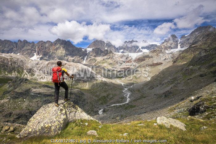 Hiker looking the peaks of the Bernina Group, Valmalenco, Province of Sondrio, Valtellina, Lombardy, Italy