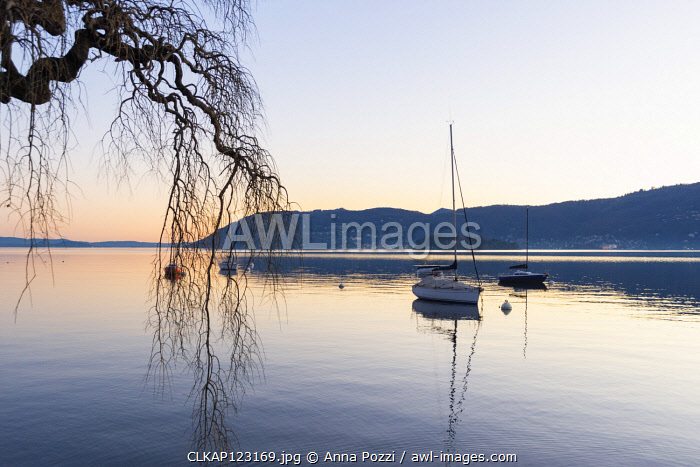 Suna, Verbania province, Piedmont, Italy Sailboat on a buoy, sunset hour