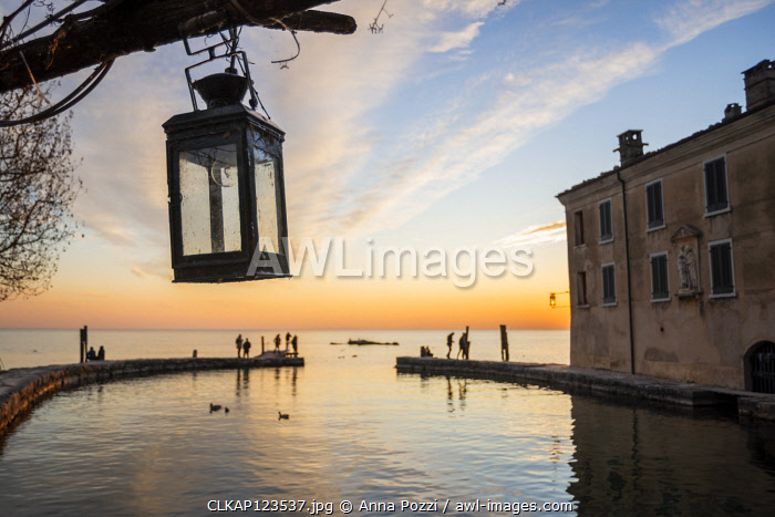 Punta San Vigilio, Verona province, Veneto, Italy An old lantern hanging from an old wooden trellis on the dock of the bay