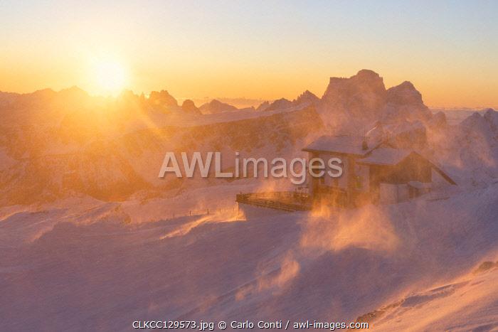 a windstorm lifts the snow in a cold winter sunrise at the Lagazuoi refuge, munipality of Cortina d'Ampezzo, Belluno province, Veneto District, Dolomiti, Italy