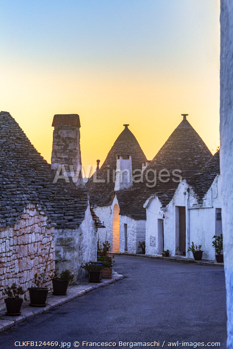 The sunrise illuminates sky above monumental trulli area. Unesco World Heritage Site, Alberobello, Province of Bari, Apulia, Italy