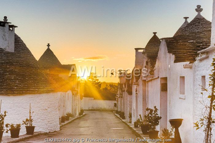 Sunrise between trulli houses. Unesco World Heritage Site, Alberobello, Province of Bari, Apulia, Italy
