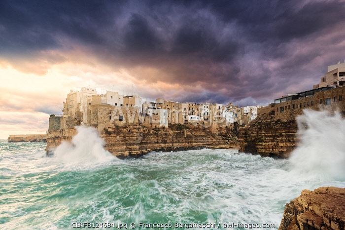 Waves crash on the cliff during a winter storm at sunrise. Polignano a Mare , Apulia, Italy