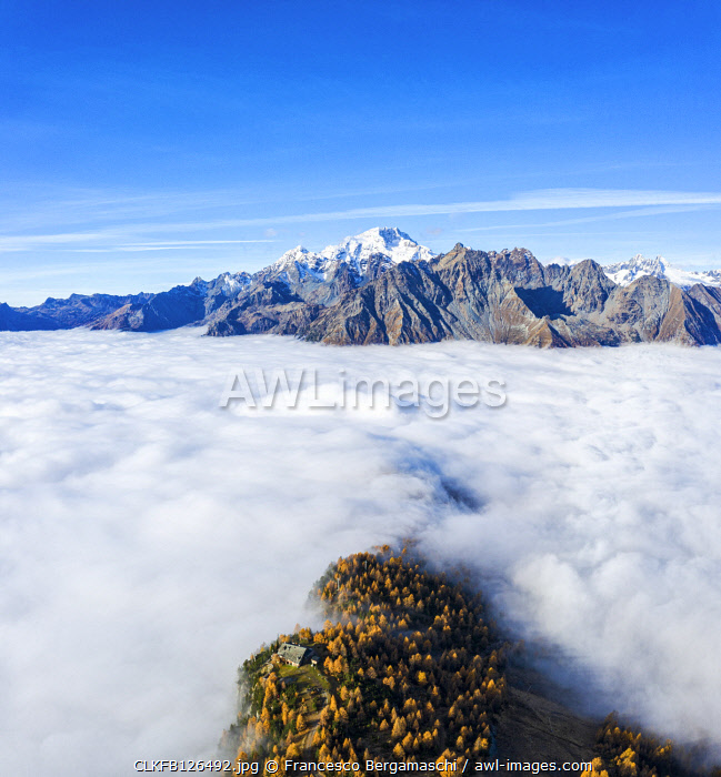 Fog covers the Valmalenco(Val Malenco) with the mountain range of Disgrazia in the background. Valtellina, Lombardy, Italy