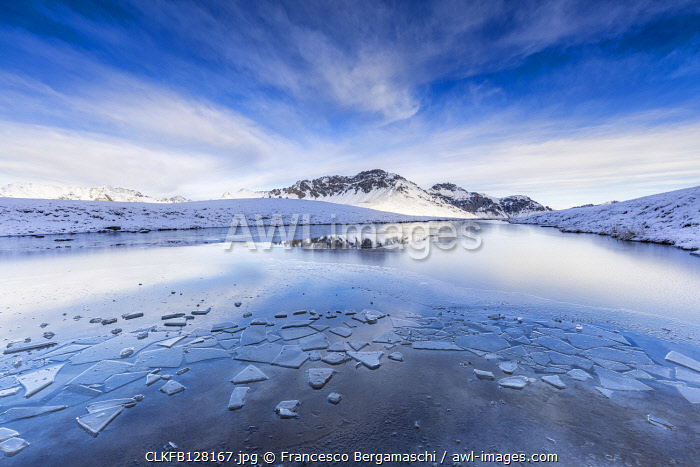 Clouds is reflected in the icy surface of alpine lake. Stelvio pass, Valtellina, Lombardy, Italy
