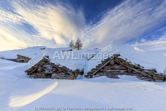 Stunning clouds at sunrise above traditional old huts in winter. Valmalenco, Valtellina, Lombardy, Italy