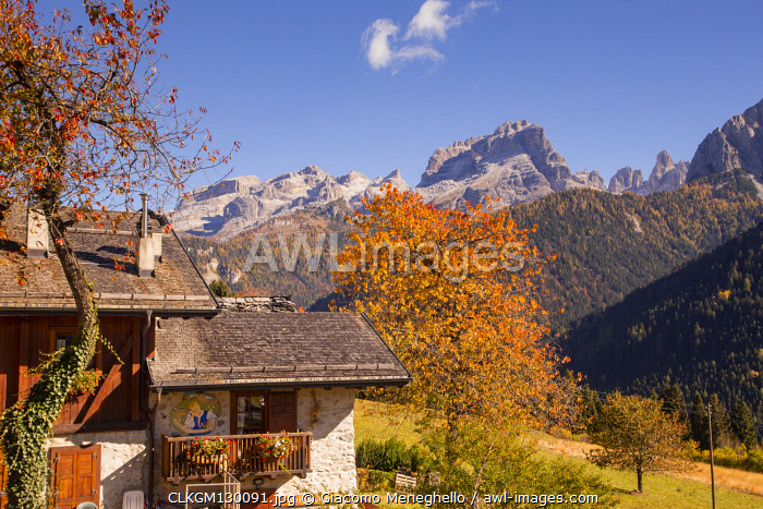Autumnal landscape of a mountain house with Brenta Dolomites in background. Madonna di Campiglio, Rendena valley, Trento district, Trentino Alto Adige, Italy