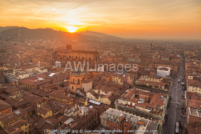 Panorama from Asinelli tower at sunset to Old city of Bologna with San Luca church in the background in backlight. Bologna, Emilia Romagna, Italy